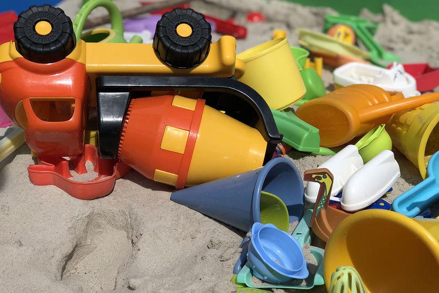 In einer Sandkiste liegen viele Sandkasten-Spielsachen durcheinander. Ein Zement-Mischer-Lastwagen liegt auf der Seite, zwei Reifen zeigen nach oben. - Copyright: Ev.-Luth. Kirchenkreis Lübeck-Lauenburg